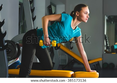 Fitness sporty young sexy Woman in gym doing exercises with dumbbells - stock photo