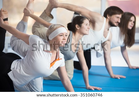 Fitness, stretching practice, group of four attractive smiling fit young people working out in sports club, doing kneeling kickbacks, exercise for lower back, hips and buttocks in class - stock photo