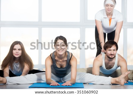 Fitness, stretching practice, group of three beautiful happy fit young people working out in sports club, doing Seated straddle posture on blue mats, instructor helping student to correct the pose - stock photo