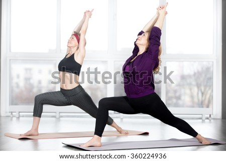Fitness, stretching practice, group of two attractive happy smiling fit mature women working out in sports club, doing Warrior 1 posture, Virabhadrasana I pose in class, full length - stock photo