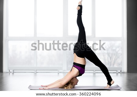 Fitness, stretching workout, attractive mature woman working out in sports club, keeping fit, doing one-legged downward-facing dog pose, eka pada adho mukha svanasana in class, full length - stock photo