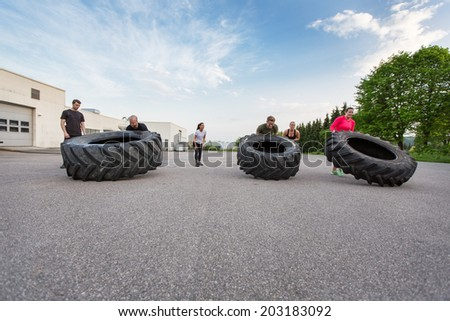 Fitness team flipping heavy tires outdoor - stock photo