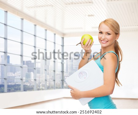 fitness, technology, people and sport concept - smiling woman with scale and green apple over gym or home background - stock photo