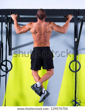Fitness toes to bar man pull-ups 2 bars workout exercise at gym - stock photo