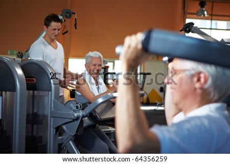 Fitness trainer coaching two senior people in a gym