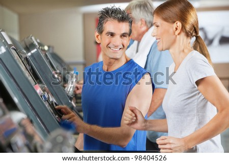 Fitness trainer explaining treadmill to jogging woman in gym - stock photo