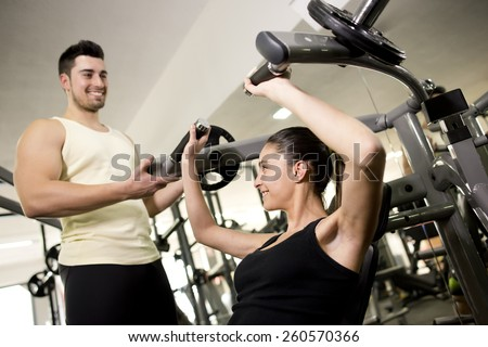 Fitness trainer helping woman in pectoral exercises. Focus is in woman, candid image with ambient light. - stock photo