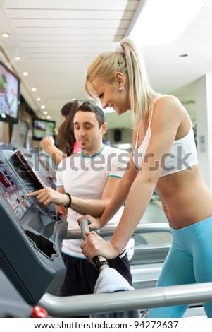fitness trainer instructing girl for setting treadmill - stock photo