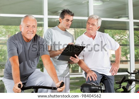 Fitness trainer with clipboard coaching happy senior people in gym - stock photo