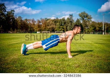 fitness trainer working out on football field. Healthy gym training outdoors - stock photo