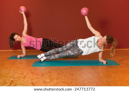Fitness Training - 2 girls using a ball for exercise