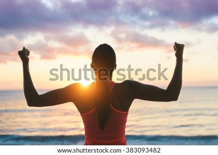 Fitness woman celebrating fitness workout success and motivation towards the sea and sunset. - stock photo