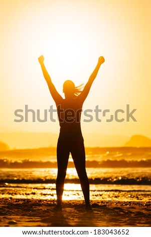 Fitness woman celebrating sport success on beautiful summer sunset or morning on the beach.  Successful female runner silhouette raising arms to the sun. - stock photo