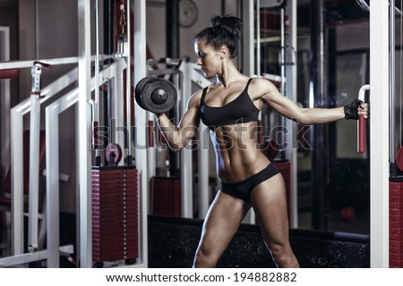fitness woman doing exercises with dumbbell in the gym. Brunette fitness girl in black sport wear with perfect body performing biceps exercises - stock photo