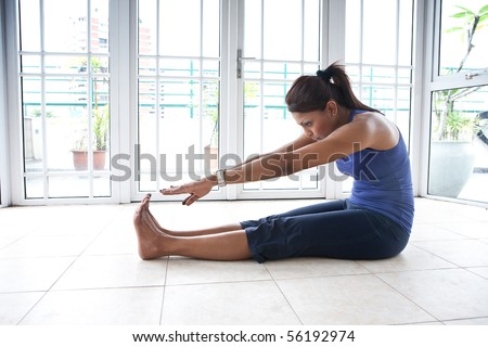 Fitness woman doing her hamstring stretch indoor - stock photo