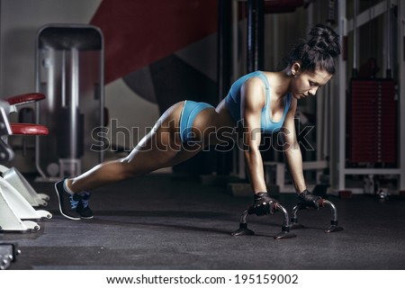 fitness woman doing push up in the gym. Brunette fitness girl in blue sport wear with perfect body performing push ups  - stock photo