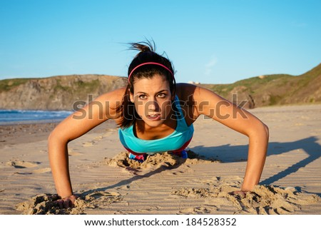 Fitness woman doing push ups at the beach on summer. Brunette sporty girl training hard. - stock photo