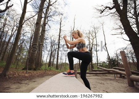 Fitness woman doing stepping up exercise in forest. Caucasian female model working out in nature. - stock photo