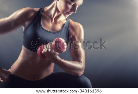 Fitness woman doing workout with weights on a dark background. Focus on dumbbell - stock photo