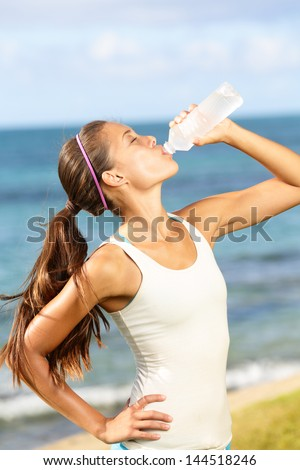 Fitness woman drinking water after running at beach. Thirsty sport runner resting taking a break with water bottle drink outside after training. Beautiful fit sporty mixed race Asian girl. - stock photo