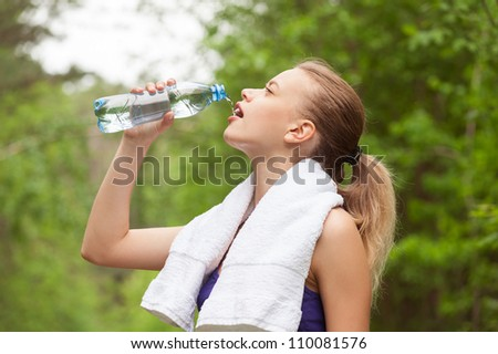Fitness woman drinking water from bottle outdoors - stock photo