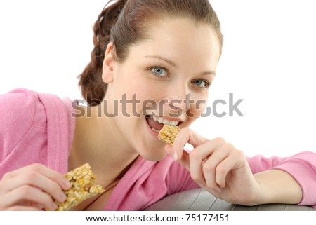 Fitness woman eat granola bar sportive outfit in gym - stock photo
