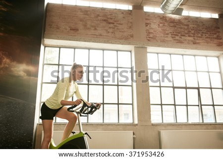 Fitness woman exercising on a spinning cycle in gym. Caucasian young female athlete doing fitness training on a stationary bike. - stock photo