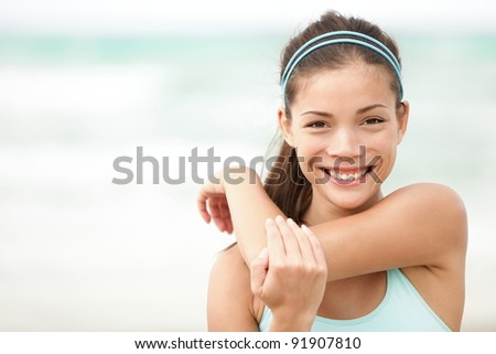 Fitness woman exercising smiling happy stretching out doing workout on beach. Beautiful mixed race Asian Caucasian female fitness model portrait. - stock photo