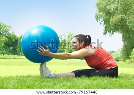 Fitness woman exercising with ball outdoors. - stock photo