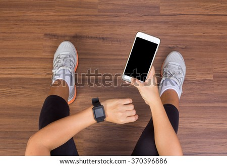 Fitness woman hand with wearing watchband touchscreen smartwatch with holding mobile phone, View from above studio shot on wooden floor background - stock photo