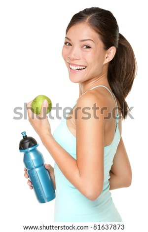 Fitness woman happy smiling holding apple and water bottle. Healthy lifestyle photo of Asian Caucasian fitness model isolated on white background. - stock photo