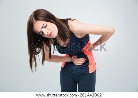 Fitness woman having pain in stomach over gray background - stock photo