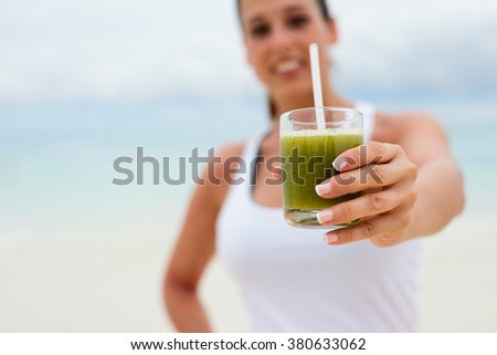 Fitness woman holding green healthy detox smoothie. Summer diet and nutrition for slim down concept. - stock photo