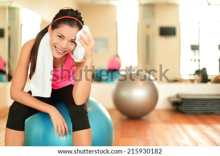 Fitness woman in gym resting on pilates ball - stock photo