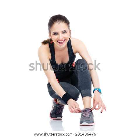 Fitness woman in sports clothes tying shoelaces isolated on a white background. Looking at camera - stock photo