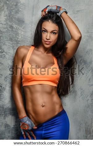 Fitness woman in sports wear posing over grey wall. Studio shoot - stock photo