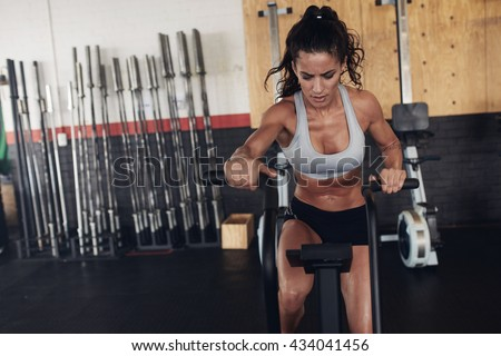 Fitness woman on bicycle doing spinning at gym. Fit young female working out on gym bike. - stock photo