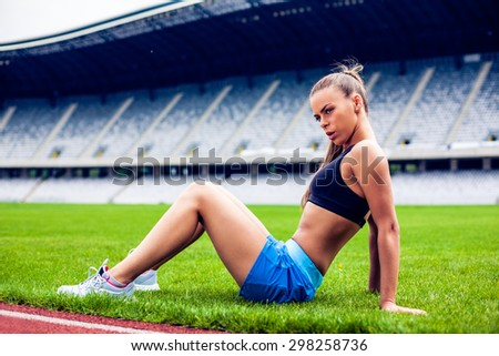 Fitness woman on stadium doing exercise  - stock photo