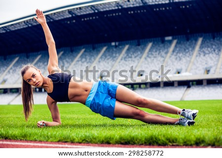 Fitness woman on stadium planking - stock photo