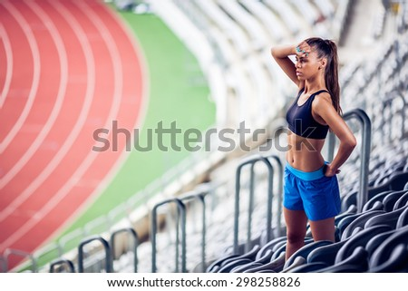 Fitness woman on stadium warming up on stairs  - stock photo