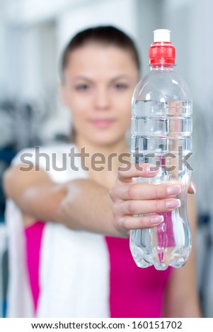 Fitness woman. Portrait of cheerful young attractive woman with bottle of water, at fitness club or gym - stock photo