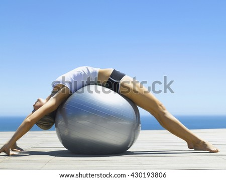 Fitness woman practicing outdoor at the sea or ocean