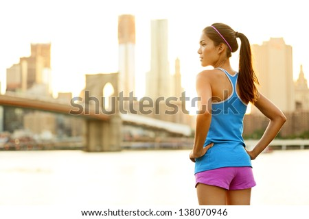 Fitness woman runner relaxing after city running and working out outdoors in New York City, USA. Girl looking and enjoying view of Brooklyn Bridge. Mixed race Asian Caucasian female model. - stock photo