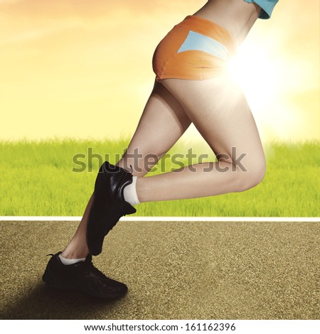 Fitness woman running at sunrise with muscular legs - stock photo