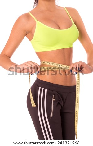 Fitness woman's beautiful body with measure tape - stock photo