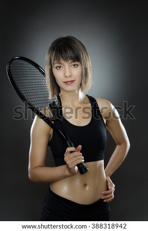 fitness woman shot in the studio low key lighting holding a tennis racket - stock photo