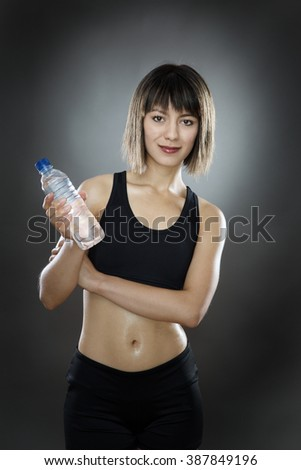 fitness woman shot in the studio low key lighting on a gray background holding a bottle of water - stock photo