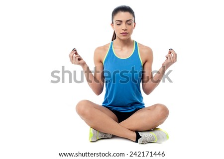 Fitness woman sitting cross legged in lotus position - stock photo
