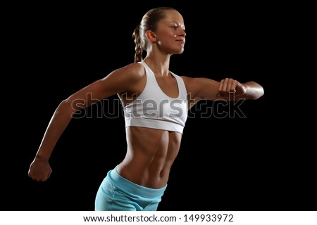 Fitness woman smiling standing against black background - stock photo