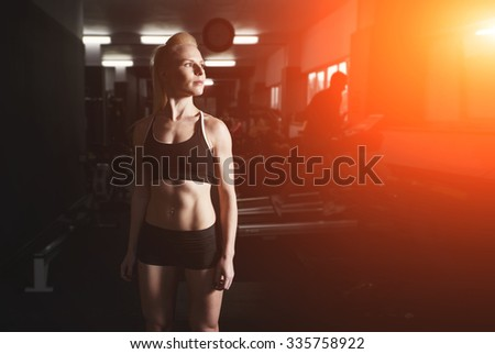Fitness woman standing in gym against sun light background. Sexy blonde fitness wet woman after workout. Girl relaxing in the gym. Young girl resting after exercises. Posters and advertising for gym.